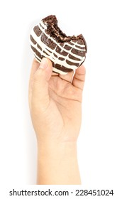 Image of chocolate cookie cake in human hand on white background