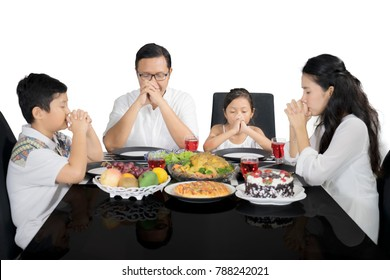 Image of Christian family praying before having lunch, isolated on white background