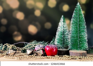 An image of a Christmas decoration green background with fir trees golden perls and red apple