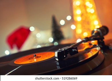 Image of Christmas. Turntable vinyl record player. Sound technology for DJ to mix & play music. Retro audio vinyl record on a background of Christmas decorations