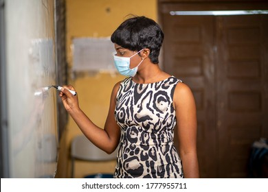 image of class teacher writing on marker board-black lady tutor in face mask after lock down-beautiful African madam with short hair in lecture room
