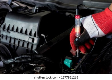 Image close up.Engine room screwdriver check fuses. A professional  mechanic is using screwdriver, check the fuses to check the operation of your car.