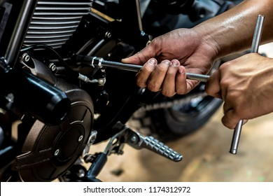 Image is Close up,People are repairing a motorcycle Use a wrench and a screwdriver to work.