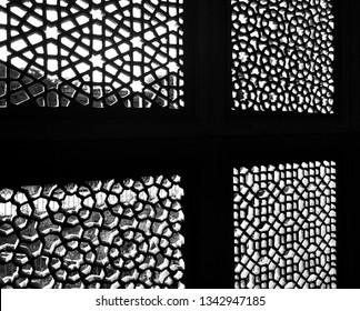The image is a close up of a window built as per Islamic architecture with motif design. The image is in Black and white