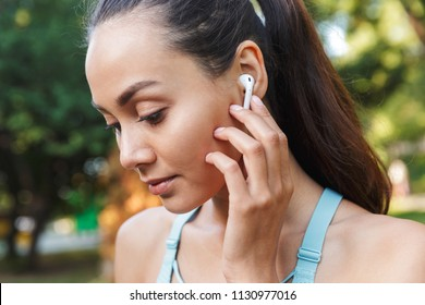 Image closeup of beautiful caucasian woman 20s in sportswear using bluetooth earbud and listening to music during walk in green park