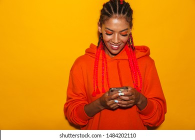 Image closeup of brunette african american woman wearing hoodie shirt smiling while holding cellphone isolated over yellow background