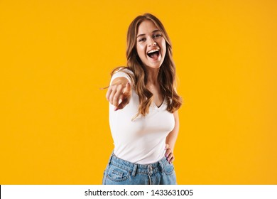 Image closeup of delighted caucasian woman wearing basic t-shirt smiling and pointing finger at camera isolated over yellow wall