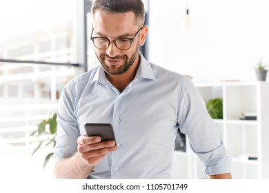 Image closeup of handsome employer man in formal wear standing in office near big window and using smartphone for work
