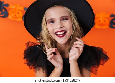 Image closeup of nice caucasian girl in black halloween costume laughing and looking at camera isolated over orange pumpkin wall