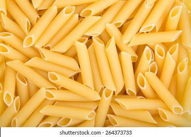 Image in close-up of raw penne pasta.