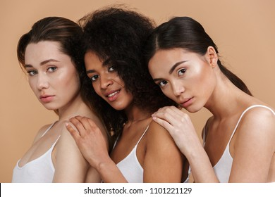 Image closeup of three gorgeous women of different nation: caucasian, african american and asian girls in basic clothing standing together isolated over beige background
