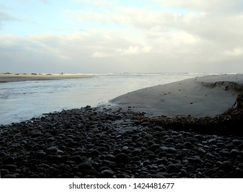 Image of coastal tidal inlet. Flowing from Pacific Ocean into San Elijo Lagoon east of this area. Shows early morning cloudy sky and low tide.