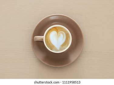 image of coffe cup with foam of heart shape over wooden table