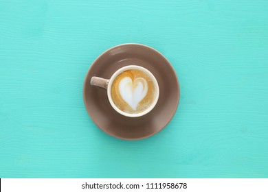 image of coffe cup with foam of heart shape over wooden blue table
