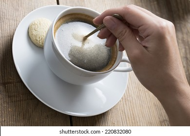 Image of a coffee cup being stirred by a white human hand, on a wooden table top