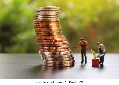 image of coins  and group of miniature mini figures grow tree to increase income and environmental care concept.