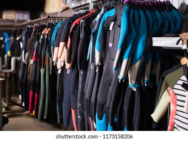 Image of colorful wetsuit hanging in the modern store for surfing