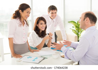Image of a company staff consulting with her boss about some working moments at the office on the foreground