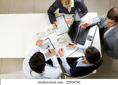 Image of company of successful partners discussing contract at meeting