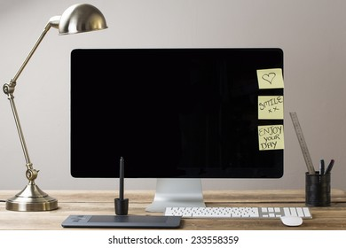 image of a computer screen with a lamp and drawing tablet, with sticky notes