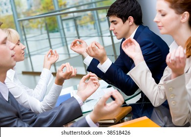 Image of concentrated business people meditating together at meeting