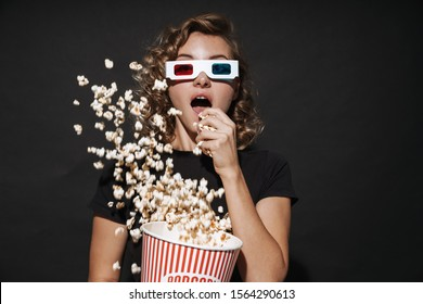 Image of a concentrated cute young woman in 3d glasses isolated over dark grey wall background eat popcorn watch cinema.