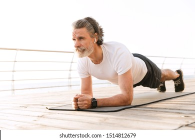 Image of concentrated mature man in sportswear using earpod while doing exercise near seaside in morning