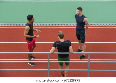 Image of concentrated multiethnic athlete group talking with each other on running track outdoors. Looking aside.