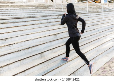 Image of concentrated muslim strong sports fitness woman dressed in hijab and dark clothes running outdoors at the street by steps.