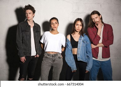 Image of concentrated young hipsters friends standing over gray background. Looking aside.