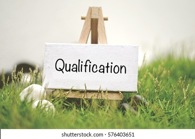 image concept white frame canvas on wooden tripod with word QUALIFICATION. Blurred and soft focus background with green grass and white stone