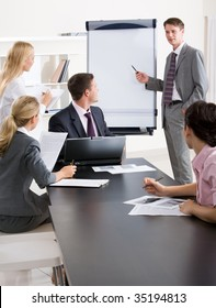 Image of confident businessman doing a presentation while their partners listening to it