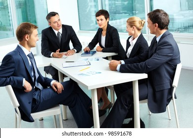 Image of confident colleagues looking at their boss at meeting
