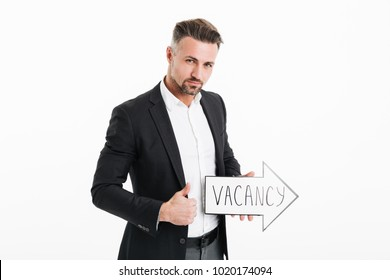 Image of confident office worker in black jacket holding speech arrow pointer with word vacancy in hand and showing thumb up isolated over white wall