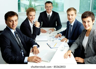Image of confident partners gathered at workplace in office