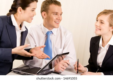 Image of confident woman explaining ideas about new project with man near by while looking at smiling employee