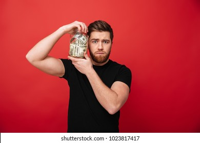 Image of confused bearded man standing isolated over red background wall holding jar full of money. Looking camera.