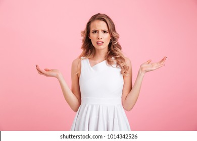 Image of confused beautiful young lady standing isolated over pink background. Looking camera.