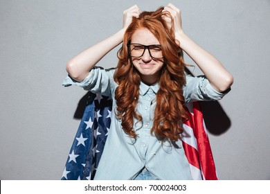 Image of confused redhead young lady holding notebook paper in hands wearing USA flag. Eyes closed.