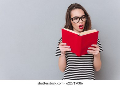 Image of confused young lady standing over grey wall reading book. Looking aside.