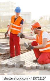 Image of construction workers with setts paving street