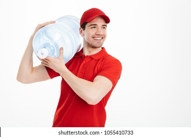 Image of content delivery courier in red t-shirt and cap carrying bottle of fresh water to office cooler isolated over white background