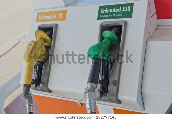 Image of a couple of petrol fuel pump nozzles on the pump at petrol station. One is unleaded E10 and has a green nozzle while the other is Unleaded 91 and has a yellow and dirty nozzle.