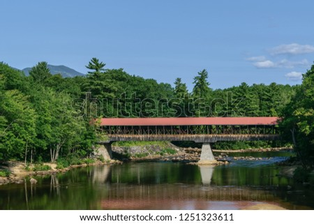 An image of a covered bridge with a red roof and stone pillars spanning a calm and quiet river casting a reflection in the water as photographed from a moving car at 65 mph.