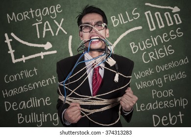 Image of crazy young businessman tied in rope and cable in the classroom