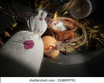 image of creepy voodoo doll laying down pierce with needles through red spots or as blood symbol on its white cloth with egg ,knife,dry foliage, 12am clock and lighting candle in blurred motion