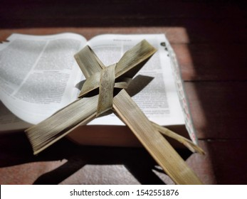 image of cross made of palm leaf on open bible under the sunlight background