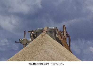 an image of a crusher working in a quarry. conveyor belt with gravel producing