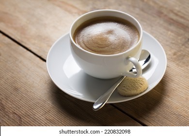 Image of a cup of coffee with an old vintage spoon and a vanilla cookie, placed on a wooden table top