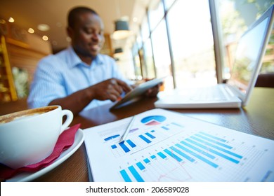 Image of cup of latte and business document on background of man using touchpad in cafe